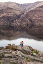 a couple standing by a lake