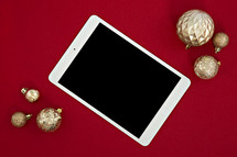 gold Christmas ornaments on a red background and tablet