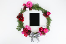 pine and flower wreath around an iPad