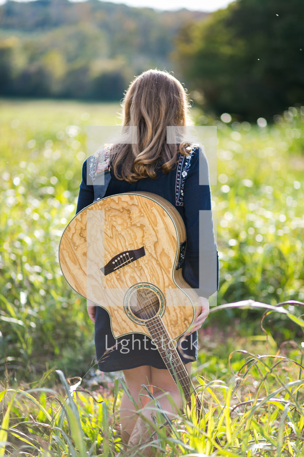 teen girl with a guitar on her back