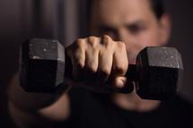 a man lifting a dumbbell towards the camera