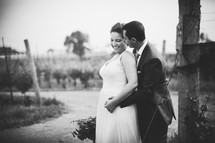 bride and groom standing in a  vineyard