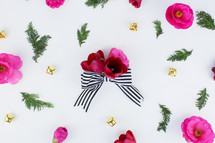 flowers, pine, and bows scattered on white background