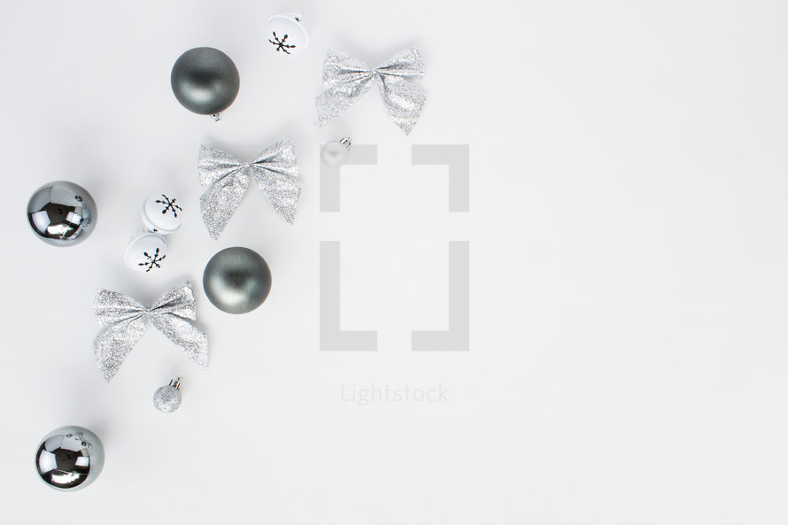 silver Christmas ornaments on a white background
