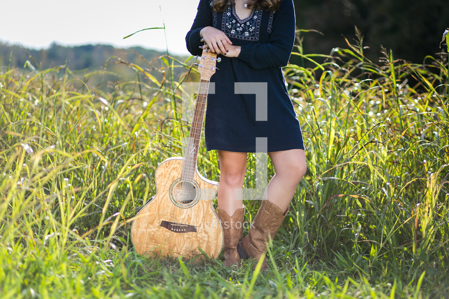 young woman with a guitar standing in a field