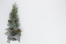 pine cones and bow on pine bough