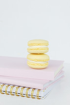 coffee and macaroons on a stack of pink notebooks