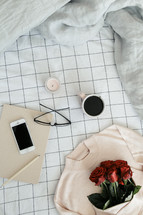 a sweater, roses, sheets, linens, bed, bedding, bedspread, iphone, planner, journal, pencil, reading glasses, candle, coffee mug, grid