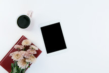 coffee mug, book, mums, and iPad on a white background