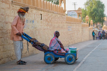 a man pushing his wife in a wagon India