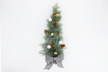 pine cones, bells, and bow on pine bough