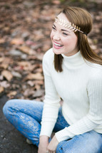 portrait of a smiling young with with a gold leaf headband
