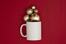 gold Christmas ornaments in a mug on a red background