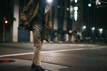 legs of a man standing outdoors on a sidewalk