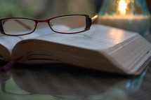 reading glasses lying on an open Bible