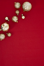 gold Christmas ornaments on a red background