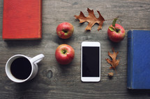 vintage books, fall leaves, iPhone, apples, on wood background