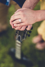 couples hands on a guitar
