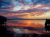 Sunset over a pier in Mount Dora, Florida reflecting off a lake at dusk.