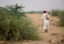 Man walking on a dirt road.
