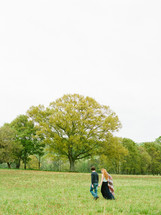 Couple walking through a field with trees.