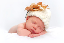 sleeping infant girl with wool hat and flower