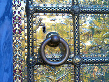 A large brass door and door knocker with the story of creation  embedded into each panel to tell  the story of Genesis and  the six days of creation. This is a beautiful brass work with much detail and history embedded in each panel of the door.