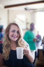 A smiling young woman holding a coffee cup.