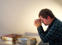 A young man bows and gives thanks in prayer surrounded by a loaf of bread and the word of God, our daily bread for living surrounded by a glowing light.