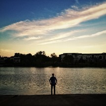 silhouette of a man standing in front of a lake