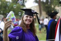 a graduate blowing bubbles