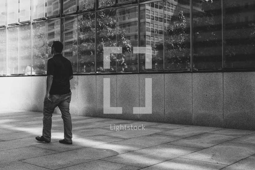 man walking past One World Trade Center
