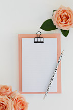 clipboard, pencil, peach roses, and blank paper