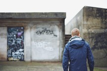 a man standing in front of graffiti covered walls
