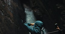 filming flowing water in a crevice between two rock cliffs