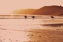 surfers walking on a beach at sunrise