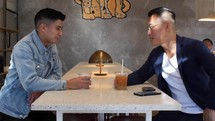 two guys talking over coffee