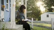 a woman sitting on reading a Bible on a porch