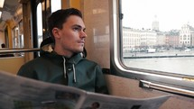 Man looking out the window of a subway train