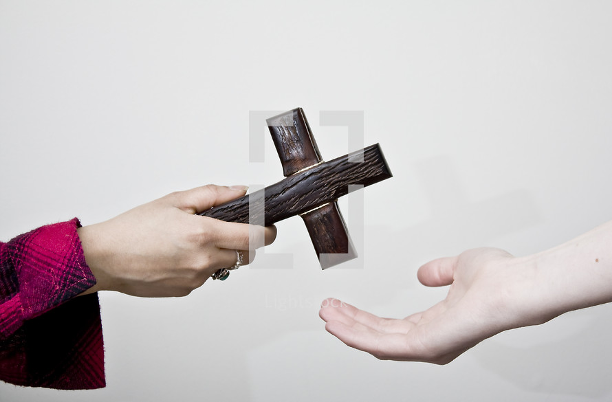 Sharing the faith; one person handing a cross to another.