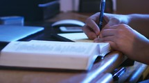 A man writing notes from Bible study at desk
