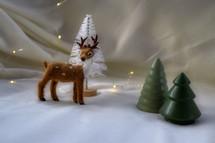 deer figurine and Christmas trees