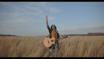 a woman standing in a field holding a guitar with her arm raised