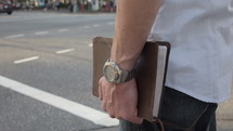 Man carries a Bible with him in the city. He is determined to carry the truth with him because it is something that impacts every part of his daily life.