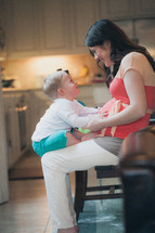 Mother holding son on her lap while sitting in a kitchen chair.