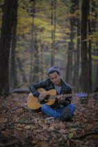 man playing a guitar in the woods