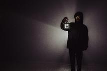 a man holding a glowing lantern at night