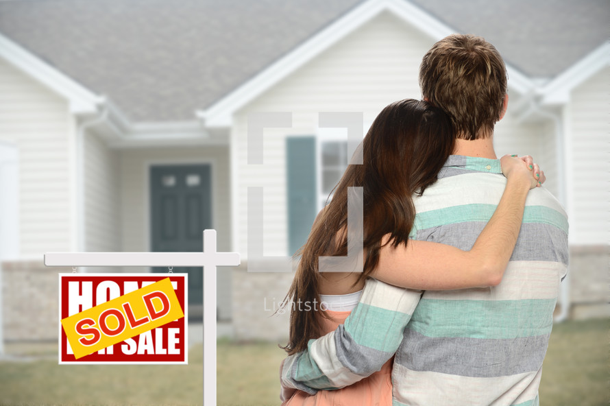 couple standing next to a sold sign in front of their new home