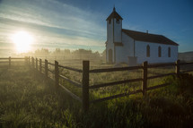 morning sunlight and a rural white church