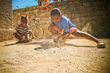 Haitian orphan plays marbles